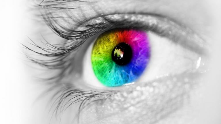 Photo of human eye with the iris in a rainbow of colors.