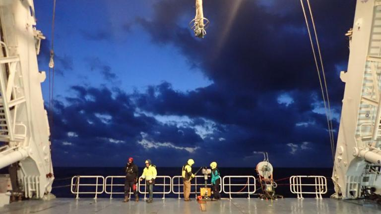 Scientists prepare to deploy an underway CTD from the back deck of a research vessel.