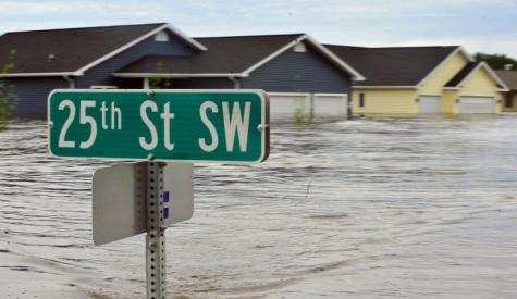 A street sign and houses are underwater due to flooding.