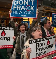 "Photo of people chanting and holding signs reading ""Ban Fracking Now."""