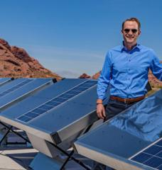 Cody Friesen standing by an installed row of installed solar-powered water harvesters