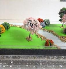 Photo of a diorama, with trees, grassy areas, and a stream, demonstrating water runoff and absorption.