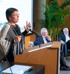 Susanne Moser, director of Susanne Moser Research and Consulting, addresses MIT's second Symposium on Climate Change. In the background are Andrew Steer, president and CEO of the World Resources Institute, and Richard Schmalensee, the Howard W. Johnson Professor of Management and Professor of Economics Emeritus at the MIT Sloan School of Management, who moderated the panel discussions.