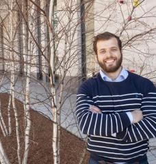 Photo of Theo Mouratidis, crossed arms, standing on MIT campus near birch trees and building